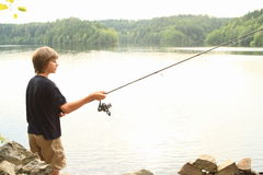 在湖的男孩捕鱼 图库摄影