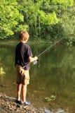 在湖的男孩捕鱼 免版税库存图片