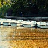 在湖的白色小船在秋天停放 库存图片