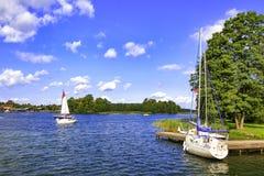 在湖的白色游艇在晴朗的夏日在特拉凯 在游艇的水上运动 与白色云彩的蓝天在有小船的湖 免版税库存照片