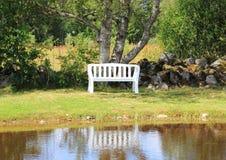 在湖的白色长凳有水反射的 免版税库存图片