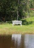 在湖的白色长凳有水反射的 库存图片