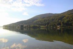 在湖的看法有在背景的山的在晴天 免版税库存照片