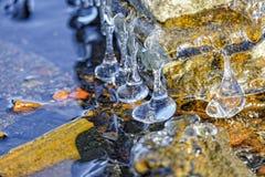 在湖的石岸形成的冰柱 库存图片