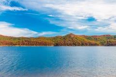 在湖的秋天季节有小山岸的美丽的森林的 免版税图库摄影