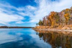 在湖的秋天季节有小山岸的美丽的森林的 免版税库存图片