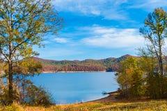 在湖的秋天季节有小山岸的美丽的森林的 库存照片