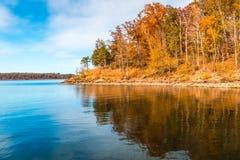 在湖的秋天季节有小山岸的美丽的森林的 免版税库存照片