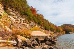 在湖的秋天季节有岩石小山岸的美丽的森林的 免版税库存照片