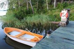 在湖的空的白橙色渔船 调遣结构树 瑞典 免版税图库摄影