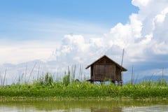 在湖的竹小屋蓝色多云天空背景的  免版税图库摄影
