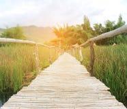 在湖的竹桥梁走道有爆炸日出光的,博士 免版税库存照片