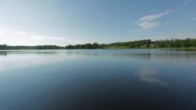 在湖的美丽的景色在夏日 深蓝湖水表面、绿色高大的树木和天空蔚蓝与白色云彩 影视素材