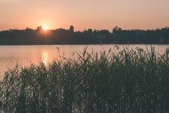 在湖的美好的夏天日落有蓝天、红色和orang的 库存照片