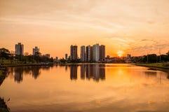 在湖的美好的温暖的日落有大厦和城市背景的 在水反射的场面 库存照片