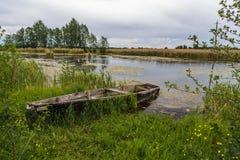 在湖的老渔船多云天气的 库存图片