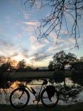 在湖的自行车剪影日落的 库存照片