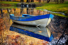 在湖的蓝色小船在秋天森林里。 库存图片