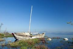在湖的被放弃的小船 免版税库存照片