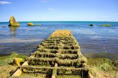 在湖的被放弃的被毁坏的木码头在黎明 免版税图库摄影