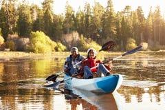 在湖的资深非裔美国人的夫妇划船皮船 库存照片