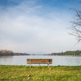 在湖的边的偏僻的长凳 免版税库存照片