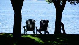 在湖的边缘的两把椅子 图库摄影