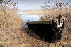 在湖的银行的木小船在早期的春天 库存照片