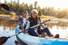 在湖的非裔美国人的夫妇划船皮船 库存照片
