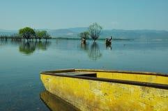 在湖的黄色独木舟 免版税库存照片