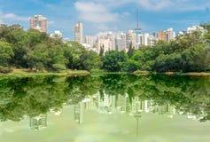 在湖的buldings反射在公园 免版税库存照片