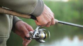 在湖的Fisher人Mishing在春天 钓鱼者举行钓鱼竿 卷在关闭被看见  股票录像