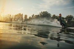 在湖的Wakeboarder滑雪日落的 免版税图库摄影
