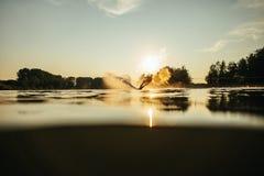 在湖的Wakeboarder滑雪日落的 库存照片
