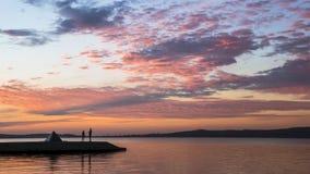 在湖码头的人剪影在日落 库存图片