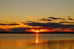 在湖背景的金黄反射日落 库存照片