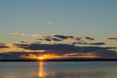 在湖背景的金黄日落 库存图片