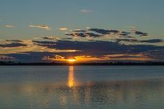 在湖背景的金黄日落 库存照片