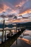 在湖跳船的火热的橙色日出 免版税库存照片