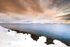 在湖边的日落与海湾的岩石在低潮期间的 图库摄影