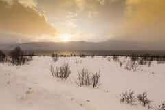 在湖边的日落与海湾的岩石在低潮期间的 库存图片