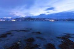 在湖边的日落与海湾的岩石在低潮期间的 免版税库存照片
