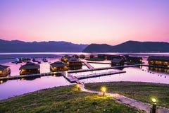 在湖边rafthouse手段的日落在Srinagarind水坝,干乍那 免版税库存图片