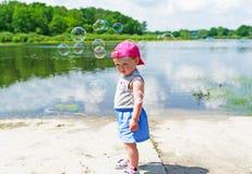 在湖银行的女孩费用  在她的泡影附近飞行 库存图片