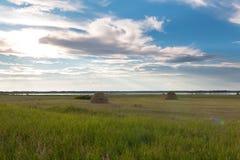 在湖附近有两个干草堆 免版税库存图片