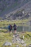 在湖附近的两个远足者步行 库存照片