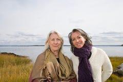 在湖附近的两名妇女 免版税库存图片