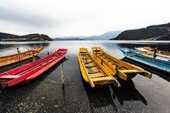 在湖附近的五颜六色的木小船 免版税图库摄影