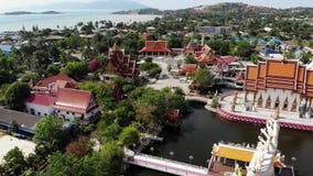 在湖附近的佛教寺庙 美妙的佛教寺庙屋顶和雕象寄生虫顶视图在湖附近的位于晴朗 影视素材