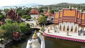 在湖附近的佛教寺庙 美妙的佛教寺庙屋顶和雕象寄生虫顶视图在湖附近的位于晴朗 股票视频